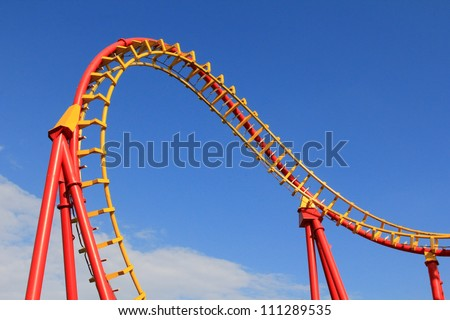 A Roller coaster track in Red and Yellow against blue sky at Prater Amusement park in Vienna, Austria - stock photo