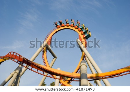 a rollercoaster doing a loop against a blue sky - stock photo