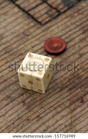 A Roman bone dice and gaming counter on a wooden table - stock photo