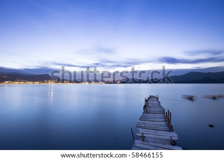 a romantic blue sunset with a jetty over a lake with an evening glow - stock photo