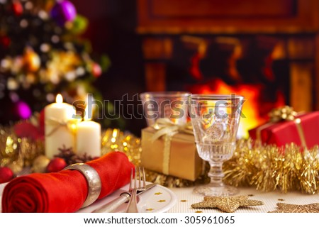 A romantic Christmas dinner table setting with candles and Christmas decorations. A fire is burning in the fireplace and Christmas stockings are hanging on the mantelpiece.