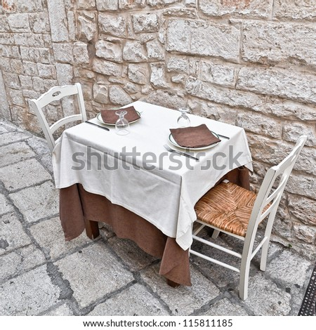A romantic dinner table in a street of urban centre in Cisternino's town, in Apulia. Italy