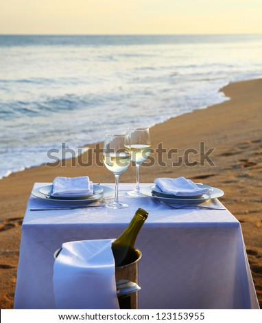 A romantic restaurant table and ice bucket on a summer beach at sunset