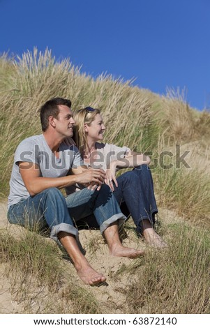 A romantic young man and woman couple sitting together in grassy sand dunes of a sunny beach with a bright blue sky