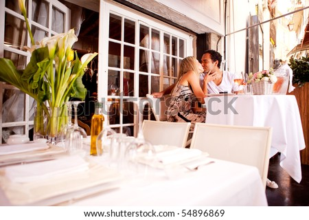 A romatic couple kissing in an outdoor restaurant - stock photo