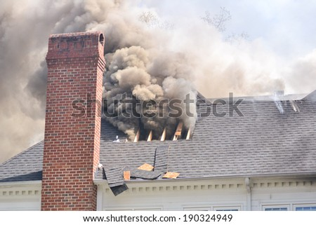 A roof has been cut open to vent heat and smoke during a training fire - stock photo