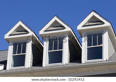 A roof line with three dormers against a blue sky - stock photo