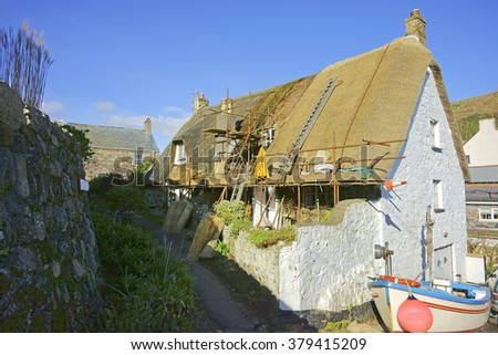 A roof of a Cottage being thatched in Cadgwith Cove on the Lizard Peninsula on the Cornwall coast, England, United Kingdom - stock photo