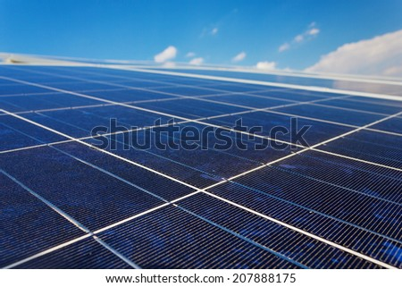 A roof with solar panels cells - detail. Solar panels producing clean and sustainable electricity. Solar panels against a serene blue sky. - stock photo