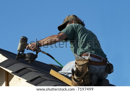 a roofer on a roof putting down shingles - stock photo