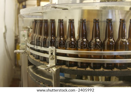 A root beer factory bottle filling line getting ready to fill bottles. - stock photo