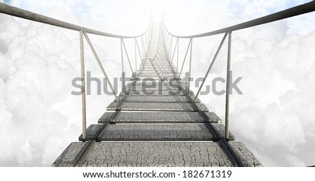A rope bridge made of wooden planks held together by rope and secured by wooden pegs above the clouds in the heavens - stock photo