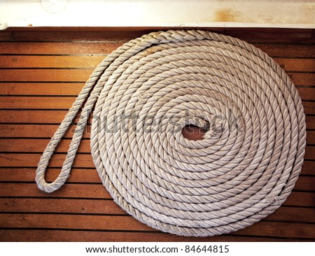 A rope coil laid across teak decking - stock photo