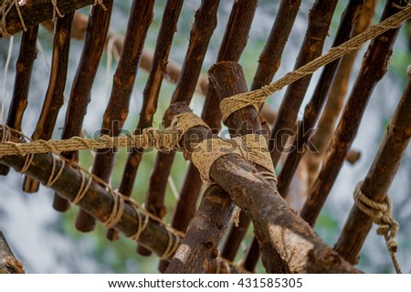 A rope is tied in a knot around a fence post  ,  rope tied knot wood pole  ,  white rope tied wood