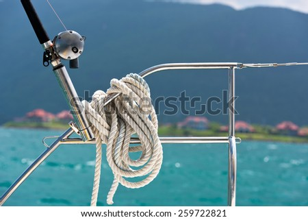 A rope tied around a lifeline and a fishing rod on a yacht. Ocean background - stock photo