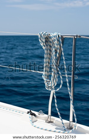 A rope tied around a lifeline on a yacht. Ocean background - stock photo