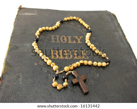 A rosary laying on a worn antique Bible. - stock photo