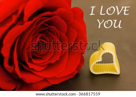 a rose and a heart against a dark background - stock photo
