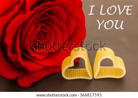 a rose and two hearts against a dark background - stock photo