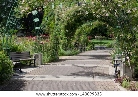 A rose garden can be seen in the distance through a rose-covered archway over a gently curved brick pathway. In Eugene, Oregon, Lane County - stock photo