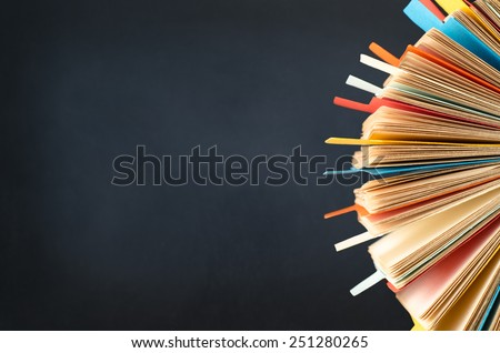 A rotating card index, filled with cards and divided with multicoloured tabs. cropped at right side of frame.  A black chalkboard background provides copy space to the left. - stock photo