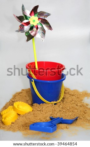 A rotating child's windmill, buckets and spades recalling seaside fun. - stock photo