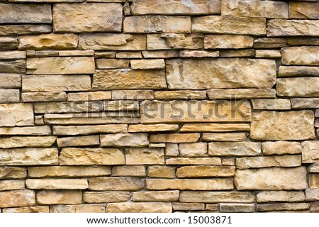 A rough stone masonry wall great for backgrounds or textures - stock photo