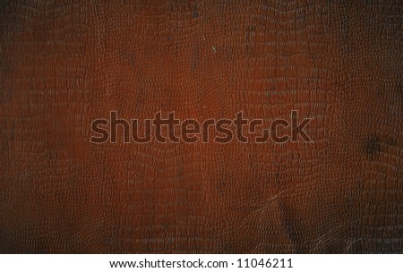 A roughened and distressed piece of brown faux crocodile leather book-cover, for use as a background texture. - stock photo