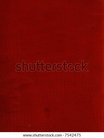 A roughened and distressed piece of red faux crocodile leather used as a book-cover. - stock photo