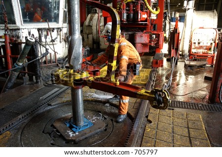 A roughneck breaking a connection with tongs, offshore oil rig - stock photo
