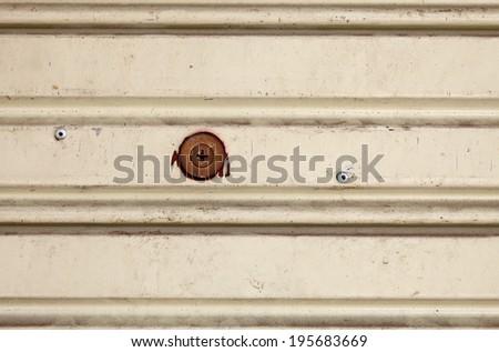 A round brass lock on a grungy pink metal shutter door.  - stock photo