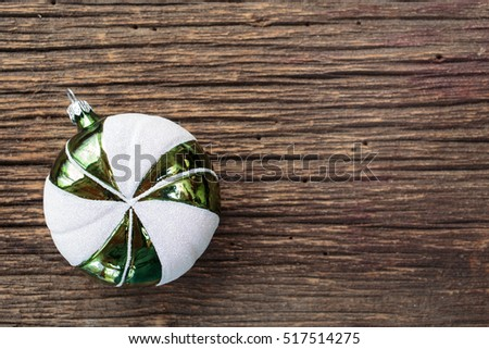 A round green and white glass Christmas ornament with wooden background and copy space.