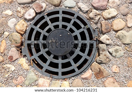A round grille sewage wells to drain rain and melt water - stock photo