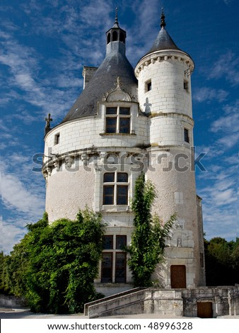 A round medieval tower with pointed turrets from Normandy, France.  The tower is white brick and stucco and has green ivy growing on the sides.  Beautiful blue sky with white clouds in the background. - stock photo