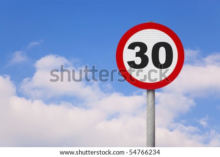A round roadsign with the number 30 on it against a blue cloudy sky.