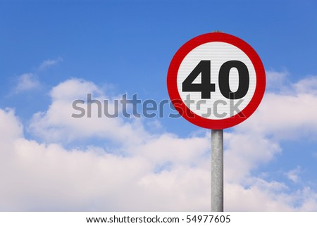 A round roadsign with the number 40 on it against a blue cloudy sky.