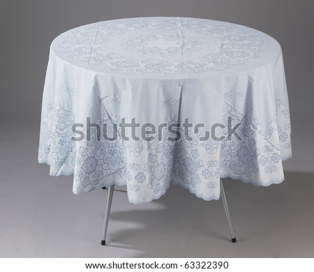 A round table covered with a table cloth - stock photo