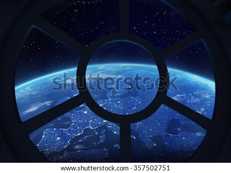 A round window on a space station with a view of Earth below - stock photo