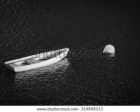 A row boat moored in a Maine harbor in black and white. - stock photo