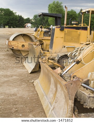 A row construction machinery on job site. Stormy skies. - stock photo