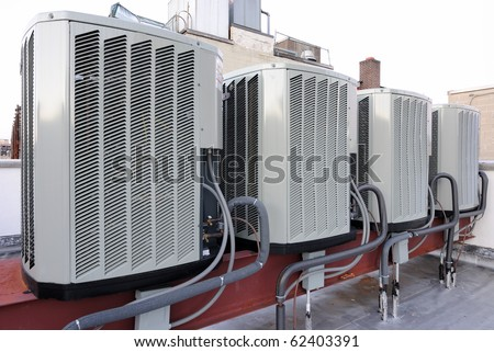 A row of air conditioning units on a rooftop. - stock photo