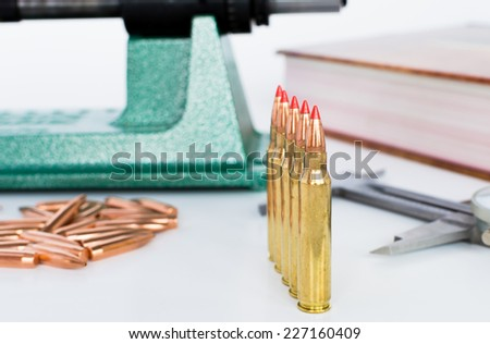 A row of ammo with reloading equipment - stock photo