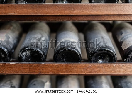 a row of ancient and tasteful dusty wine bottles in a cellar - stock photo