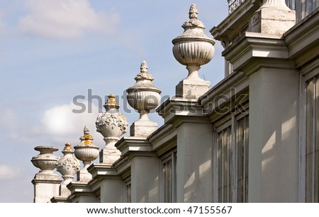 A row of architectural adornments on top of the  columns on the facade of an old building