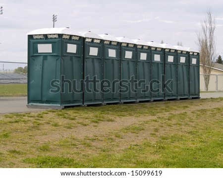 A row of bathrooms at a big event. - stock photo