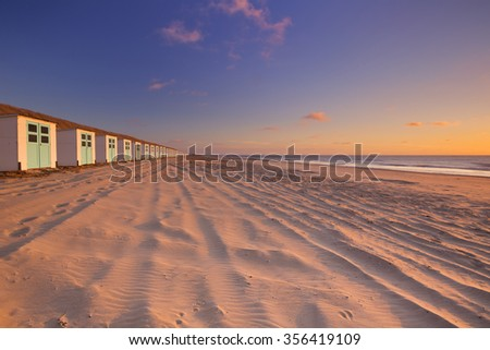A row of beach huts on a beach on the island of Texel in The Netherlands. Photographed at sunset.
