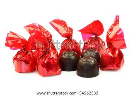a row of bonbons wrapped in red shiny paper and three unwrapped ready to eat on a white background