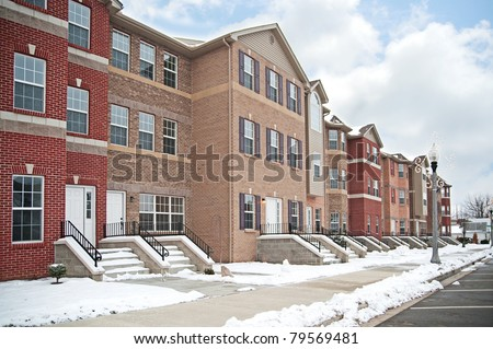A row of brick apartment condominiums in winter with snow on the steps and curb. - stock photo