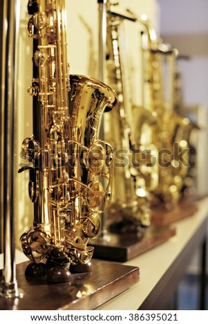 A row of bright golden saxophones in a music shop.