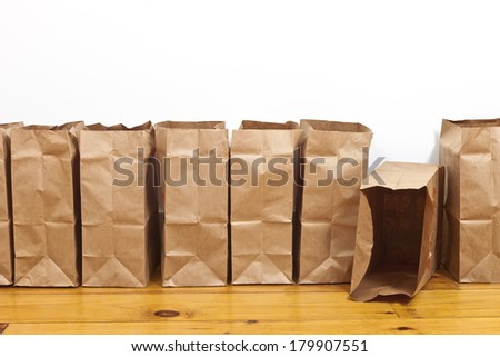 A row of brown paper bags. - stock photo